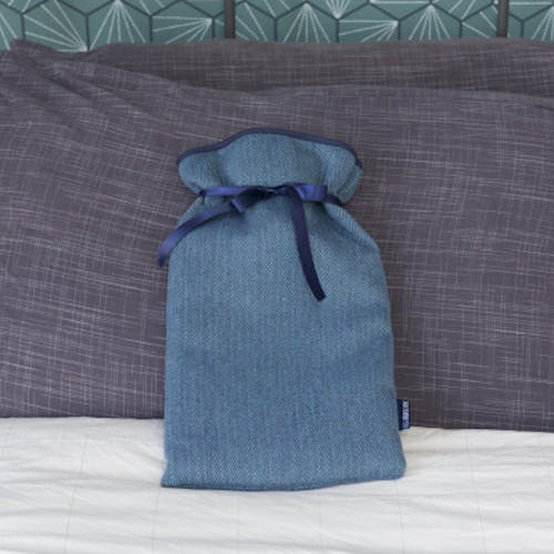 Hot water bottle in a soft blue cover with a satin ribbon sat on a bed prodded up against grey cushions