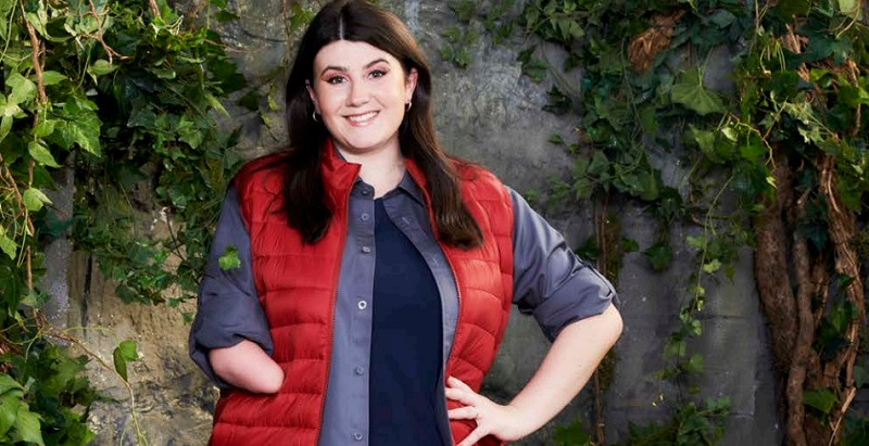 Hollie Arnold in a red puffer jacket and blue tops with her limb difference showing standing in front of a wall covered in leaves ready for I'm a Celebrity 2020
