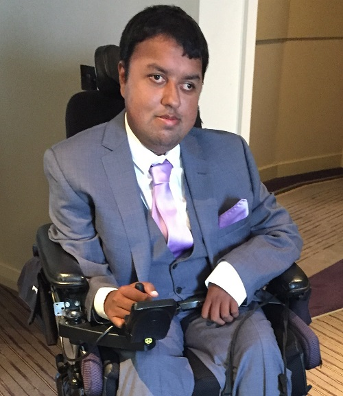 Nirav Shah in his wheelchair wearing a grey suit in a hotel room