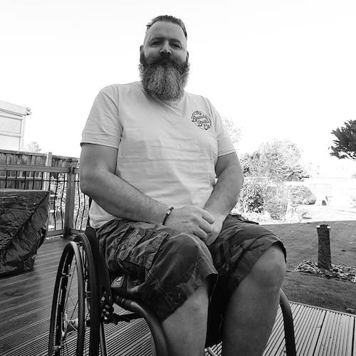Zec Richardson with a bushy beard sat on a garden deck in his wheelchair in a white T-shirt and camouflage trousers