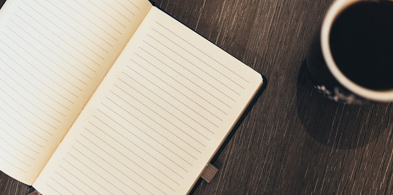 Blank notebook on a table next to a coffee mug