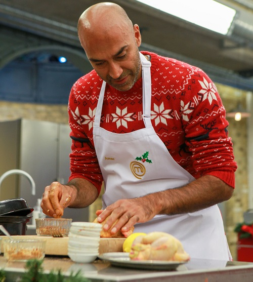 Blind presenter Amir Latif on Celebrity MasterChef Christmas special wearing a red Christmas jumper and white apron at a cooking station with ingredients
