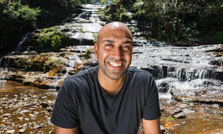 Blind presenter Amir Latif sitting on rocks in front of a waterfall