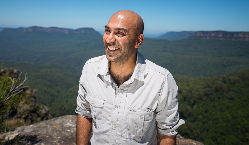 Blind presenter Amir Latif in a white short-sleeved shirt stood up high on a mountain with expanse of jungle behind him looking off to the left into the distance