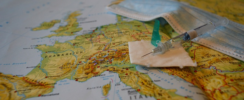 Covid-19 vaccine and face mask lying on a map of the world