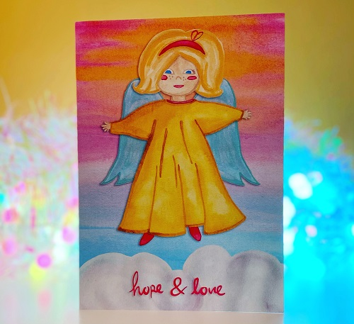 Handmade Vintage Angel Christmas card with an angle in a yellow dress with blue wings, blonde hair and blue wings floating above a cloud that says hope & love on it