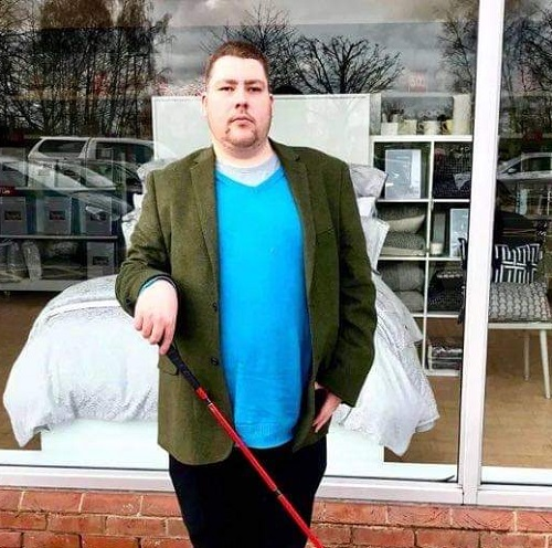Visually impaired blogger Luke Sam Snowdon wearing a bright blue T-shirt, green jacket, and black trousers with his red cane stood in front of a shop window