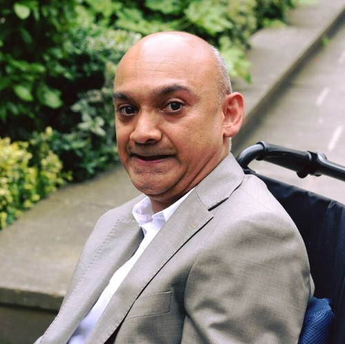 Wheelchair user Sandip in his wheelchair wearing a white shirt and pale grey suit sat in front of some greenery