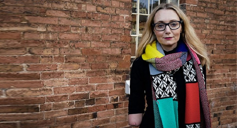Carrie Brunell wearing a black top and colourful scarf stood in front of a brick wall