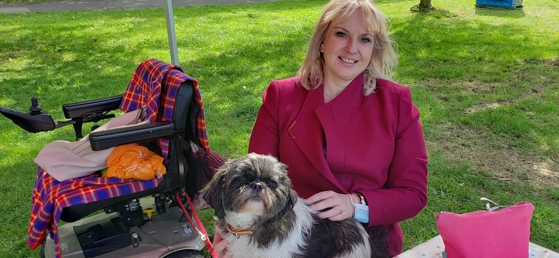 Emma Shepherd wearing a pink coat sat on a bench in a park with her dog on her lap and her mobility scooter behind her
