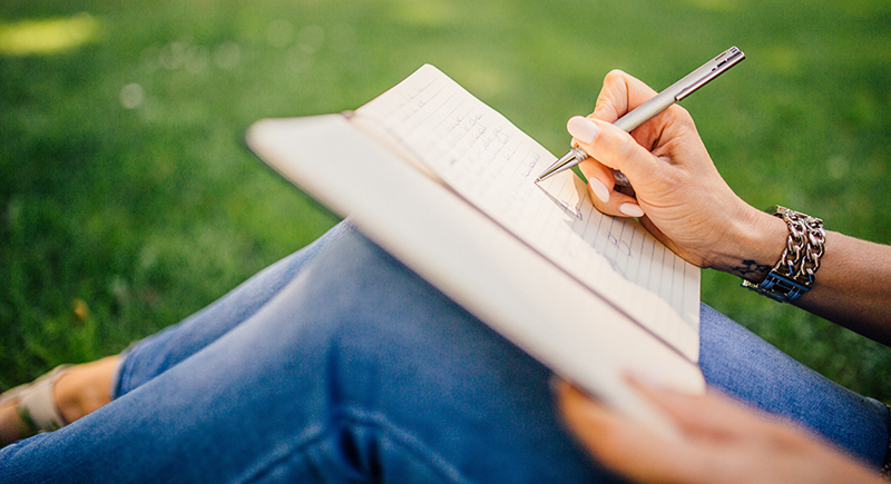 Lady writing in journal - by Negative Space