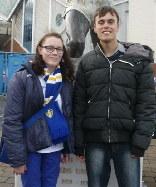 Sam and Ella at a football match outside the stadium both wearing dark puffer jackets and jeans
