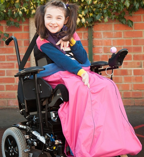 Young girl with bunches sat in her wheelchair with a bright pink Seenin fleece wheelchair cover