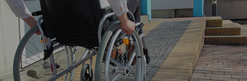 Wheelchair user going up a paved ramp in a manual chair being viewed from behind