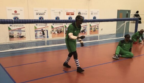 Yahya Siyad playing Goalball wearing a blindfold, green T-shirt and shorts, black and white socks and black shoes, in a sport's hall
