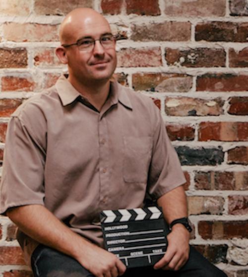 gough stood against brick wall holding film clapper board