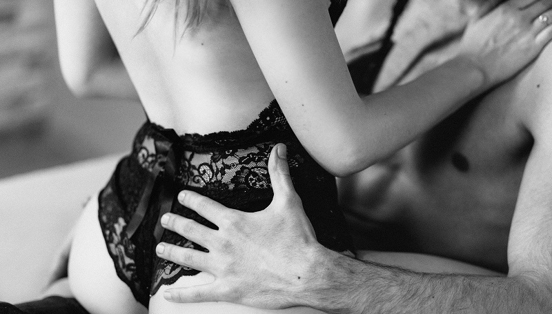 Black and white close up image of woman's bottom in lace knickers sitting on a topless man's lap facing him