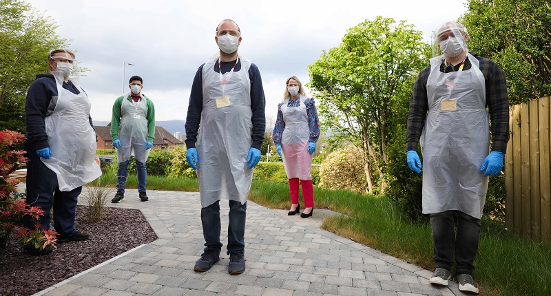 Five care staff at Leonard Cheshire stood outside wearing medical face masks, face shields, plastic gloves and plastic aprons