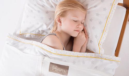 Girl lying under a Fidgetbum weighted blanket