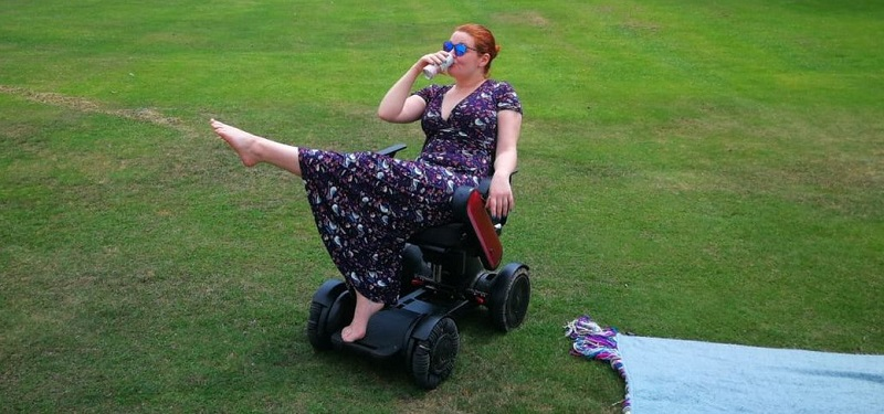 Hannah Barham-Brown in her wheelchair in a park wearing a long black dress with a floral pattern one leg in the air and drinking from a cup