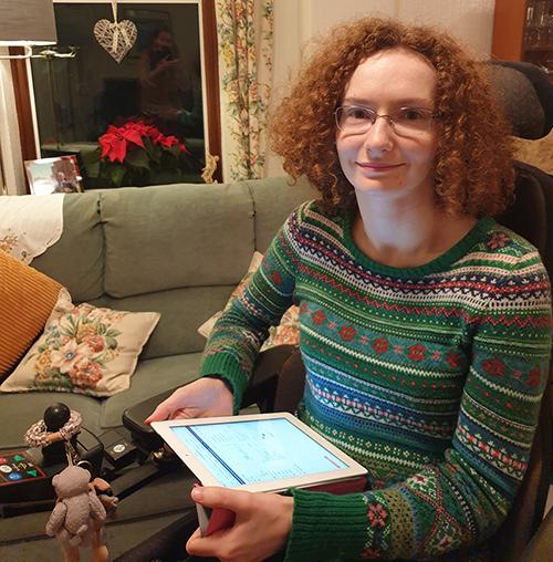 Hannah Deakin, smiling, wears a seasonal patterned winter jumper and holds her iPad
