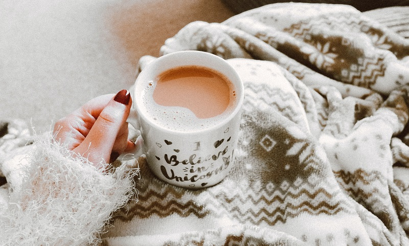 Mug of tea on a woman's lap covered in a grey fleece blanket