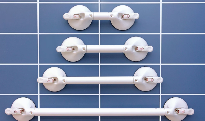 Four different sizes of Mobeli grab rails stuck onto a wall with smooth blue tiles