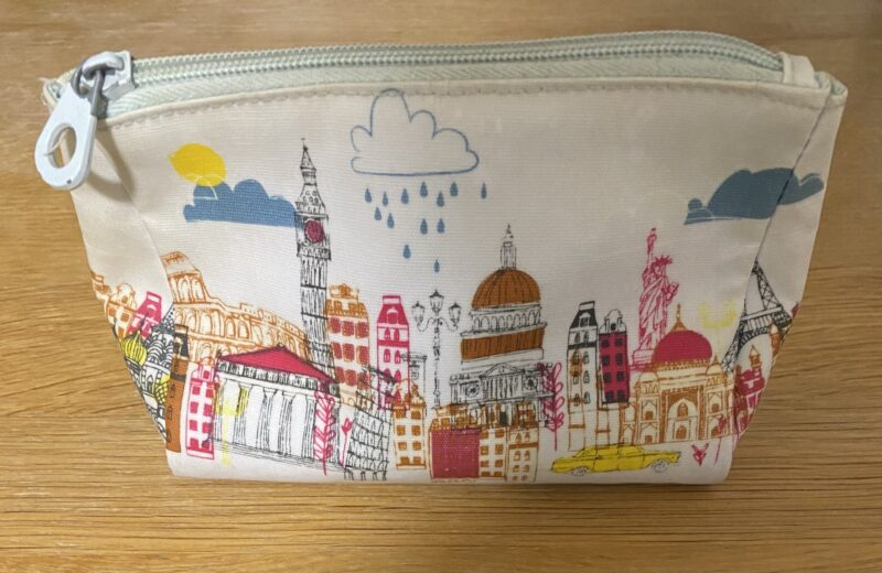 White cosmetic bag with colourful silhouette of London in pinks, yellows and orange
