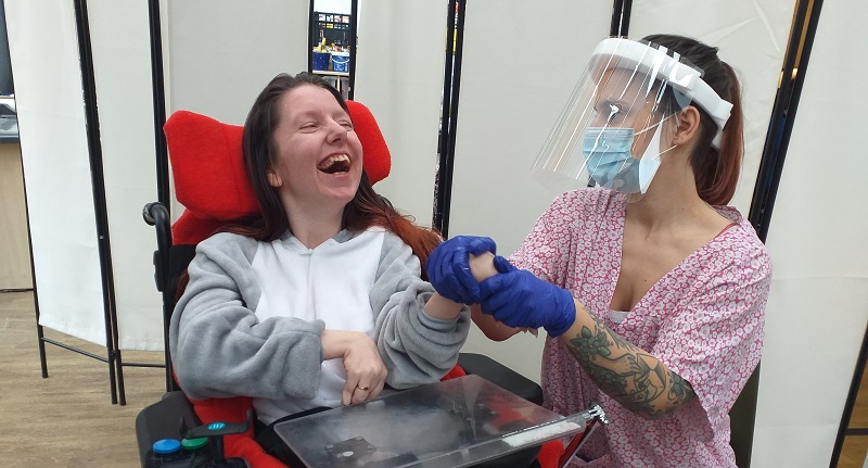 Woman in a wheelchair and grey jumpsuit with a carer wearing plastic gloves, a medical mask and face shield