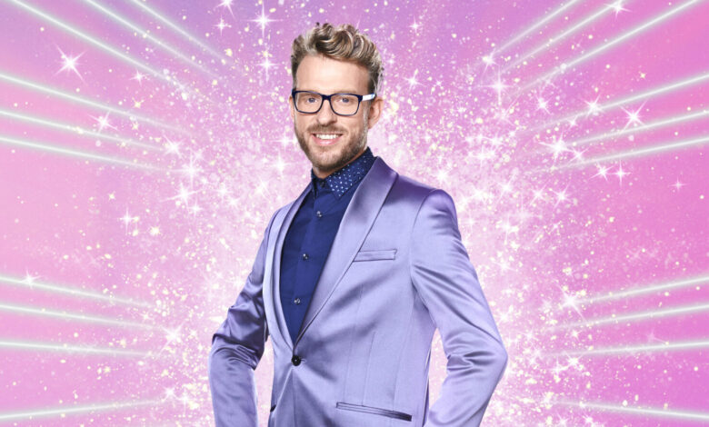 JJ Chalmers in a lilac suit and blue shirt stood in front of a pink, sparkly background