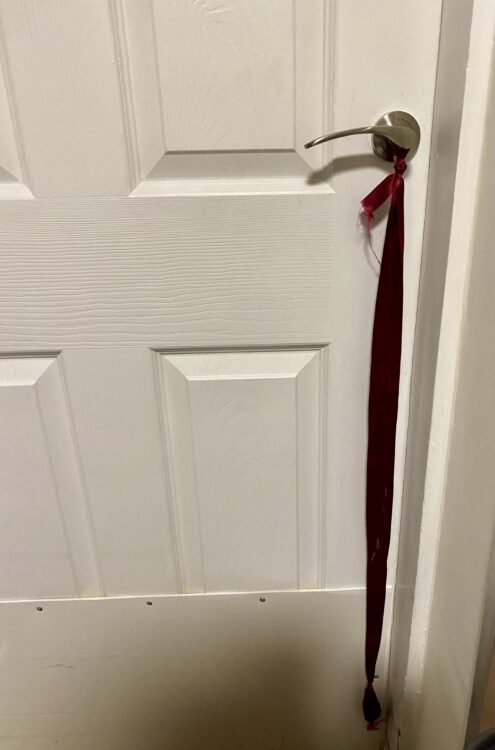 Long red ribbon tied to a door handle