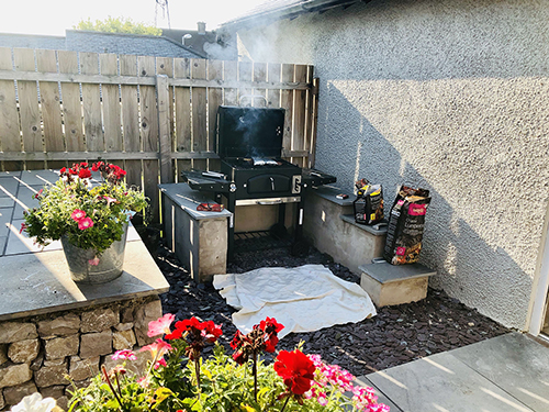 A barbeque sits in the corner of a beautiful garden