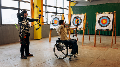 A lady and a man in a wheelchair are doing archery - Photo by Mikhail Nilov from Pexels