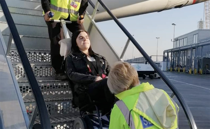 A lady is being transfered in her wheelchair inside of an airplane