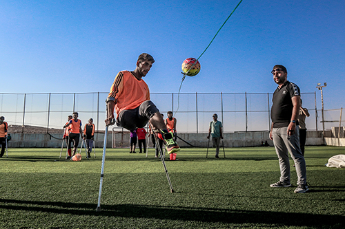 A man, who is an amputee and uses crutches, is playing football - Photo by Anas Aldyab from Pexels