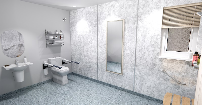 Accessible bathroom in an adapted modular home extension with grey floor and wall tiles, a toilet with supports, walk-in shower and shower chair