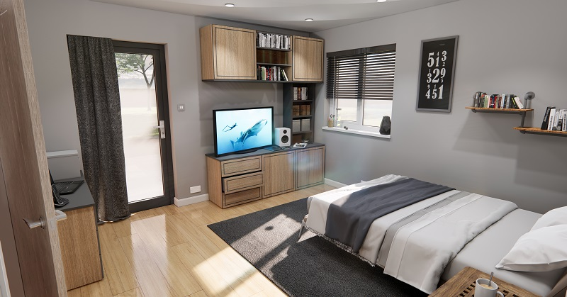Accessible bedroom in an adapted modular home extension with lots of floor space, wooden flooring, a double bed and storage cabinets on the floor and wall
