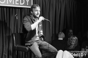 Black and white image of Chris McCausland sat on a stool performing at the Slaughterhouse