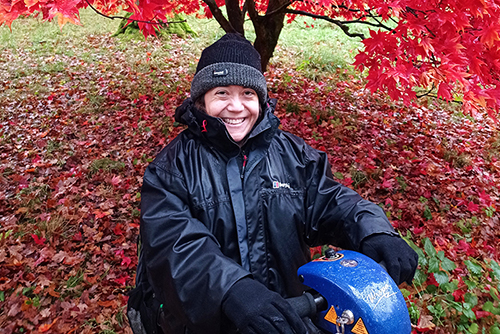 Emma is sitting on her scooter under a beautiful red tree - Photo by Emma West