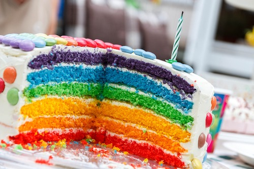Rainbow birthday cake with one candle - Image by Steffen Zimmermann from Pixabay