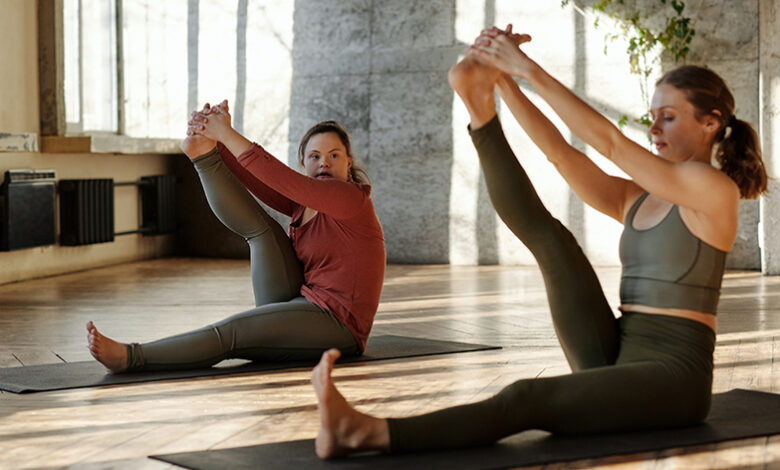 Two women are sitting on yoga mats doing leg stretches - Photo by Cliff Booth from Pexels
