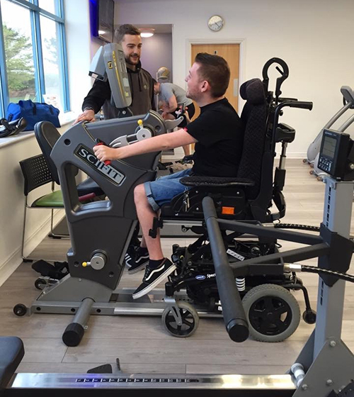 Ross is sat in his wheelchair and is using a pedal bike