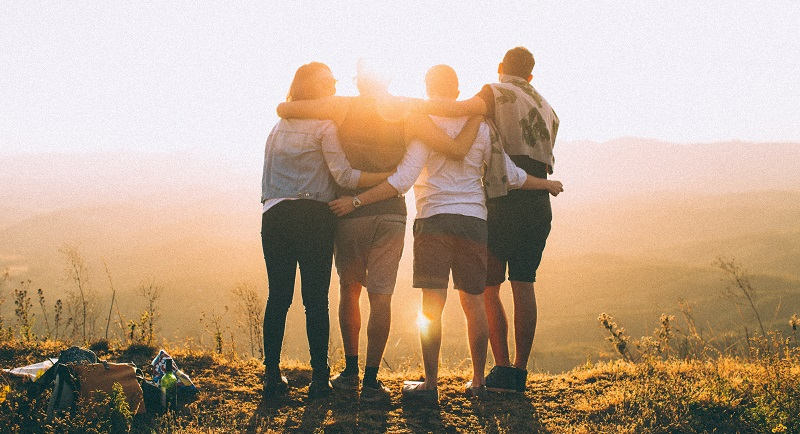 Four people stood on a cliff looking over mountains at sunset