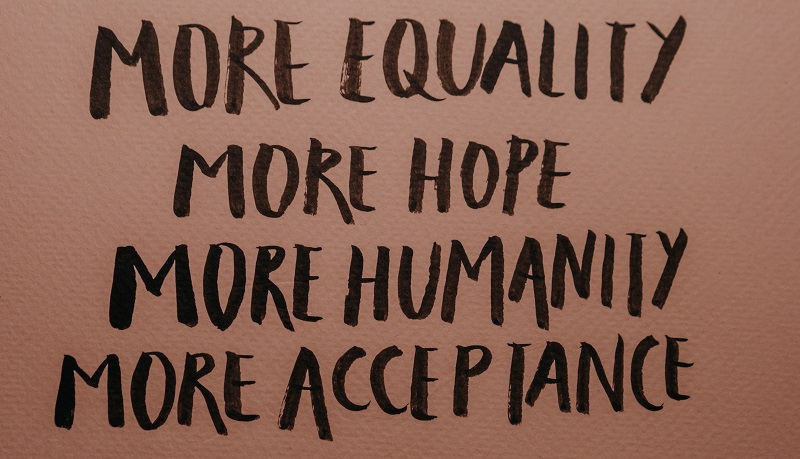 More equality, more hope, more humanity and more acceptance written on pink paper