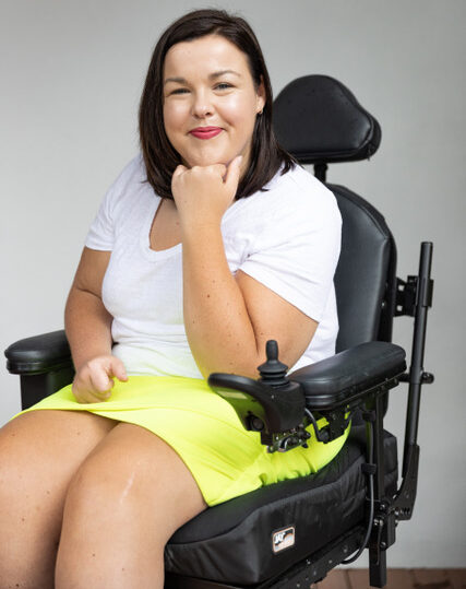 Peta Hooke in her wheelchair wearing a short yellow skirt and white T-shirt with short straight brown hair