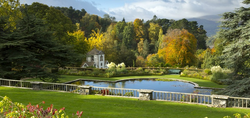 Bodnant wheelchair-accessible gardens in Wales showing formal gardens with a large pond looking out over woodland