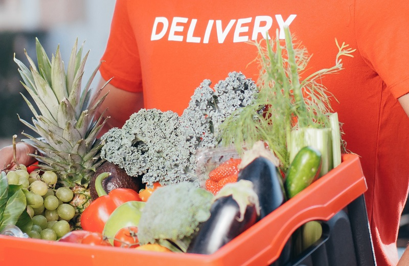 Man in an orange t-shirt with the word delivery on it delivering a box filled with food