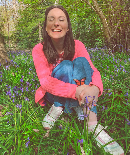 Rebecca is sitting in long grass, surrounded by flowers and is wearing a pink cardigan and jeans