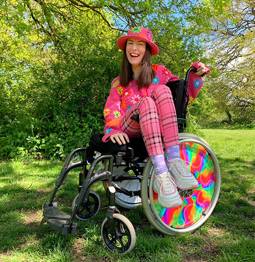 Rebecca is sitting sideways in her wheelchair, is wearing a pink outfit and is sat under a tree