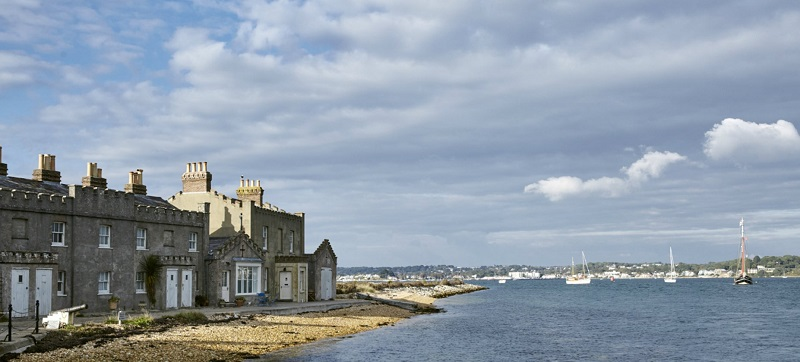 Wheelchair accessible Brownsea Island with a row of stone houses on the shore with the sea in front